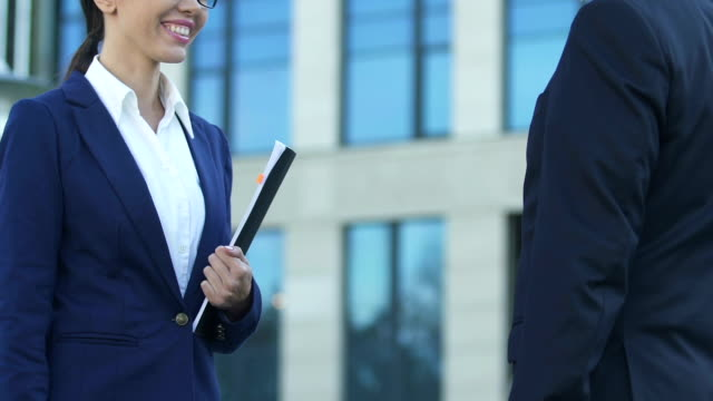 Female employee shaking hands with boss, happy for promotion, successful career