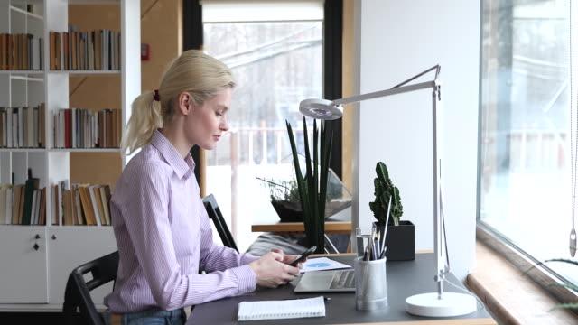 kvinnlig anställd sitter vid skrivbordet chattar använda mobiltelefon - e post bildbanksvideor och videomaterial från bakom kulisserna