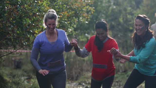 Female Empowerment A group of three women holding hands and supporting each other on the muddy fun run and smiling and sharing a celebratorty smile prop stock videos & royalty-free footage
