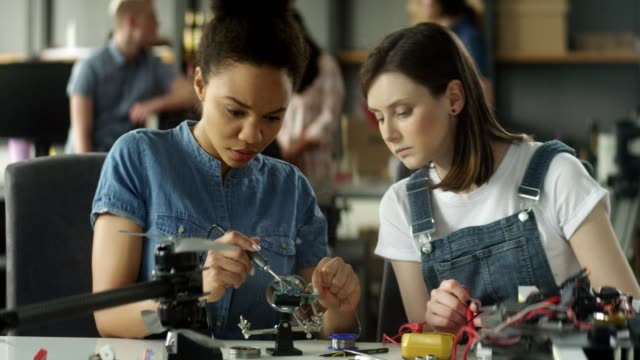 Female engeneers soldering and working on a project video
