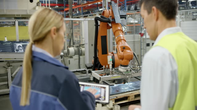 Female engineer and representative of the company manufacturing robots inspecting the performance of the industrial robots