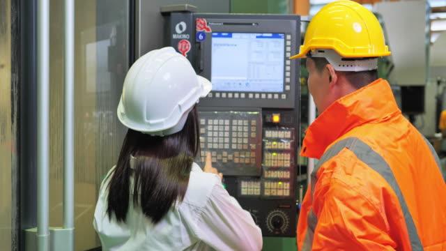 cnc機械のエンジニアと一緒に働く女性エンジニア見習い - オペレーター 日本人点の映像素材/bロール