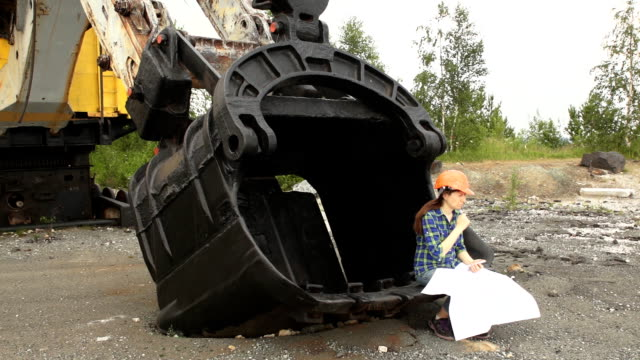 Female engineer examines a scheme sitting in a large bucket of a excavator. video