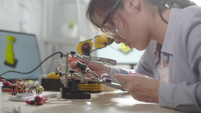 Female Engineer girl repairing the circuit board with soldering iron and wire