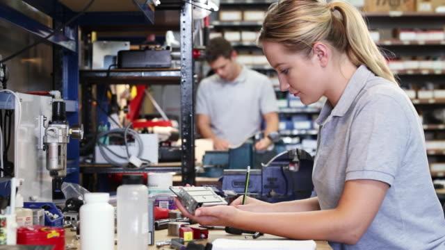 kvinnlig ingenjör i fabriken mätning komponent på arbetsbänk med mikrometer - arbetsverktyg bildbanksvideor och videomaterial från bakom kulisserna