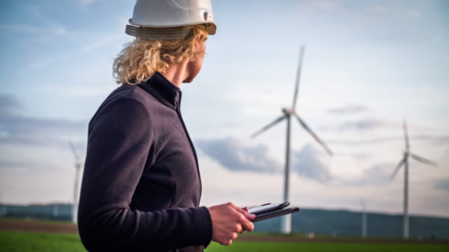 female engineer in front of wind turbines - women in stem - turbina a vento video stock e b–roll