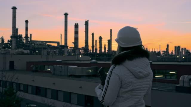 stockvideo's en b-roll-footage met ms vrouwelijke ingenieur in hardhat met digitale tablet op raffinaderijdak bij schemering - chemische fabriek