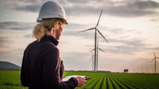 female engineer inspecting wind turbines - women in stem - turbina a vento video stock e b–roll