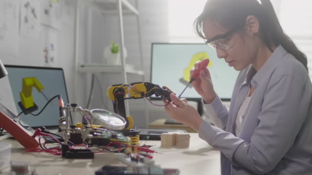 Female engineer is working on innovative technology mechanical Robot arm in his workshop,She using Digital tablet controlling Robotic arm by her hand