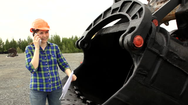Female engineer standing next to a ladle of a excavator and examines a scheme video