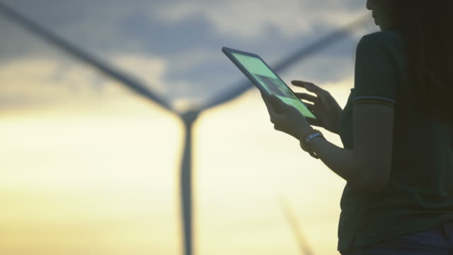 female engineer using tablet computer outdoors on wind turbines background. - энергия ветра стоковые видео и кадры b-roll