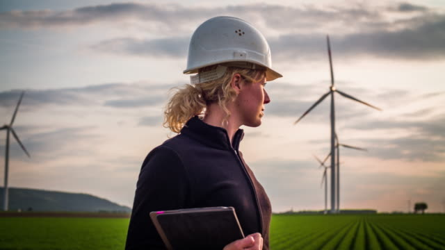 Female engineer with digital tablet in front of wind turbines