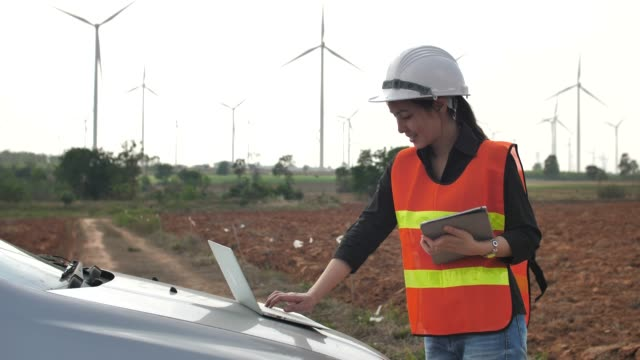 female engineer with laptop in front of wind turbines - energia rinnovabile video stock e b–roll