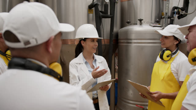 Female engineer working at a brewery explaining the process to a group of manual workers in training
