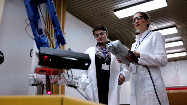 Female engineers working with robotic arm in lab