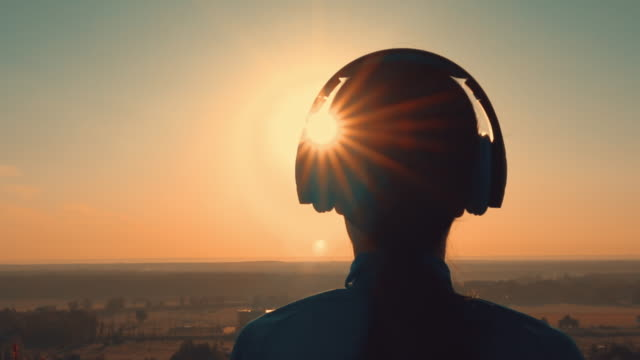 female enjoy music outdoors slow motion close up back view of woman head headphones listening music at sunrise warm landscape with orange sunlight mental wellbeing stock videos & royalty-free footage