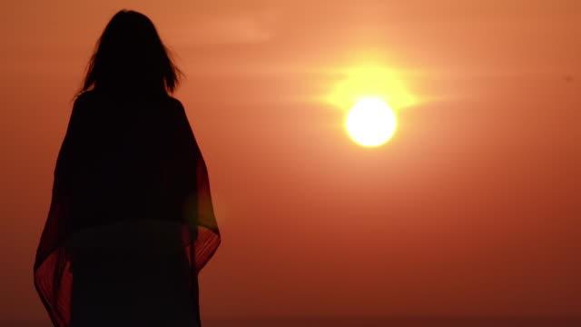 kadın yükselen güneş ile turuncu gökyüzü keyfini çıkarın - i̇nsan sırtı stok videoları ve detay görüntü çekimi