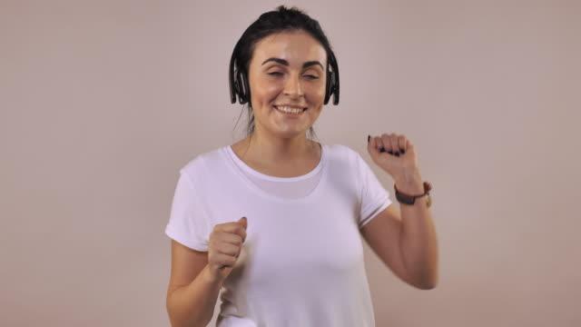 stockvideo's en b-roll-footage met vrouw geniet van zang en dans - wit t shirt