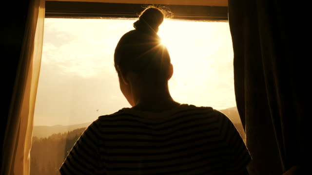 Female enjoying a beautiful morning. Young woman relaxing and enjoying the beautiful view near the window. sunrise dawn stock videos & royalty-free footage