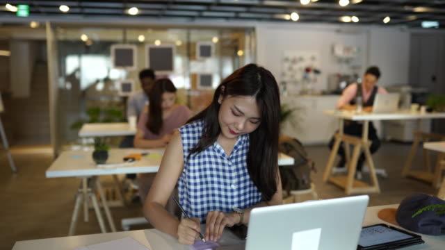 Female entrepreneur writing notes in office