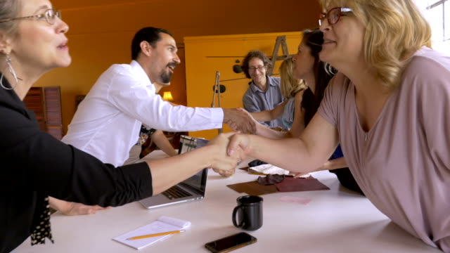 Female entrepreneurs shaking hands with investors during a collaborative meeting video