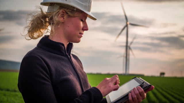 vídeos y material grabado en eventos de stock de ingeniera ambiental mujeres delante de aerogeneradores - mujeres en tallo - energía eólica