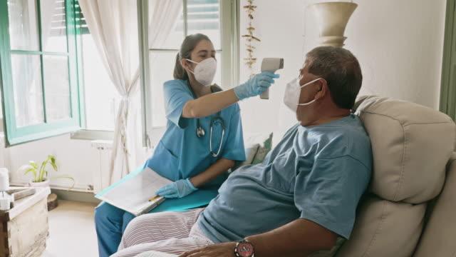 Female Essential Worker Taking Temperature of Senior Man
