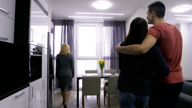 Female estate agent showing apartment to couple video