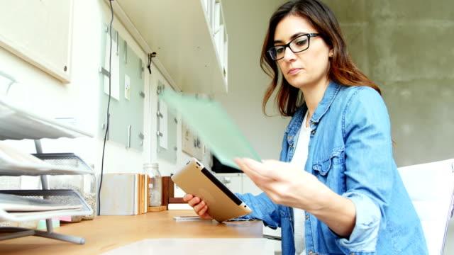 vidéos et rushes de exécutif femme regardant la feuille de verre tout en utilisant la tablette numérique - pots de bureau