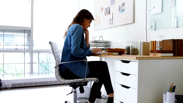 Female executive sitting at desk and using digital tablet video