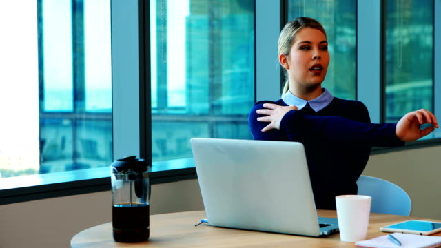 Female executive stretching her hands while working in office video