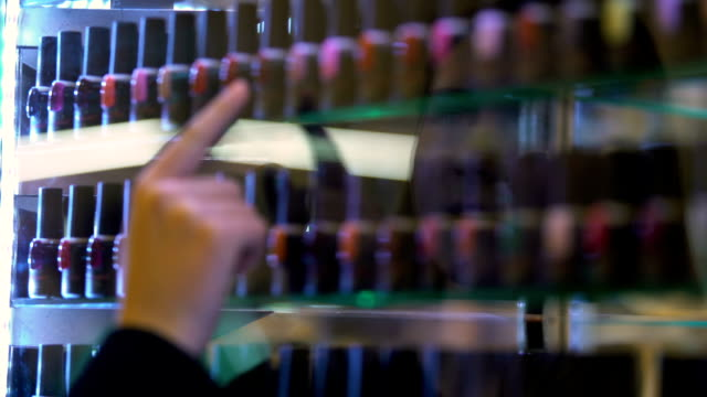 Female exhibition visitor searching for nail polish color show case, femininity
