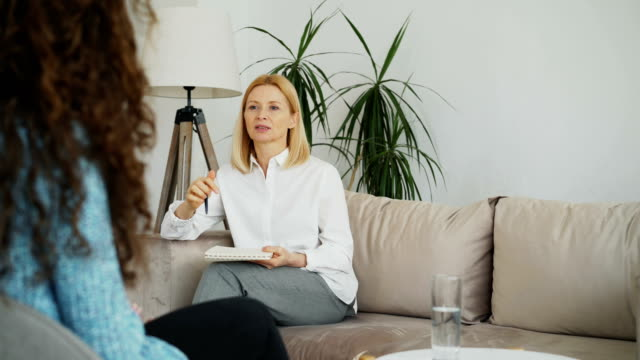 女性経験の話の心理学者と女の子の患者を混乱させるリスニングと屋内で彼女のオフィスでクリップボードにメモを書き込む ビデオ