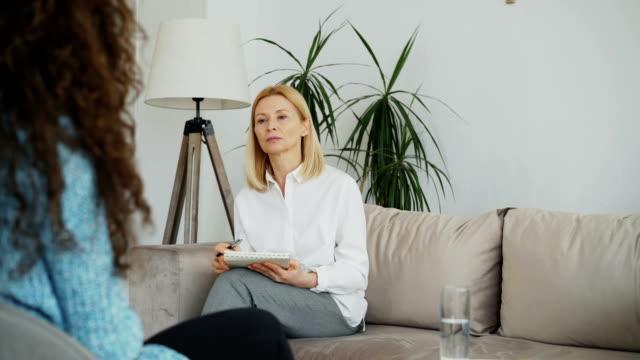 vídeos y material grabado en eventos de stock de psicólogo experimentado mujer hablar y escuchar a paciente mujer y escribir notas en el portapapeles en su oficina en el interior - profesional de salud mental