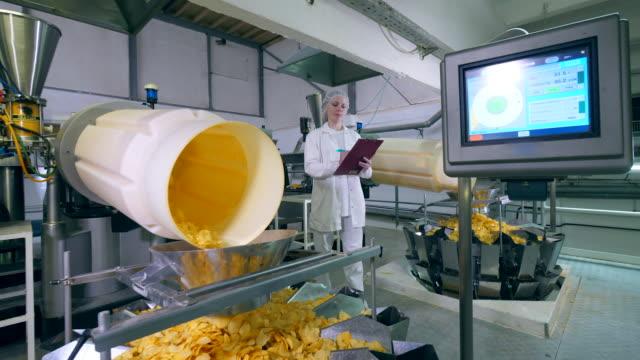 kvinnlig expert är observation process för att producera chips - livsmedelstillverkningsfabrik bildbanksvideor och videomaterial från bakom kulisserna