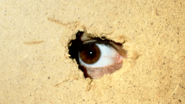 Female eye looking through hole in wall Female eye looking through hole in wall. Close-up hiding stock videos & royalty-free footage