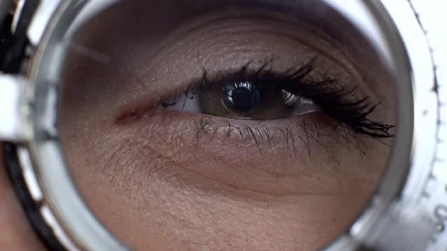 vidéos et rushes de oeil féminin regardant par le plan rapproché optique de cadre d'essai, correction de vision, lentille - réfracteur