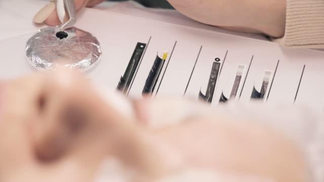 female eye with sellotape for eyelashes extension procedure. - {{relatedsearchurl(carousel.phrase)}} video stock e b–roll