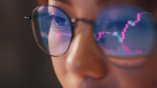 kvinnliga ögon i glasögon sent på natten rullar framför bärbar dator. kodare, hon kontrollerar bitcoin prisdiagram på digital utbyte på smartphone. - blockkedja bildbanksvideor och videomaterial från bakom kulisserna
