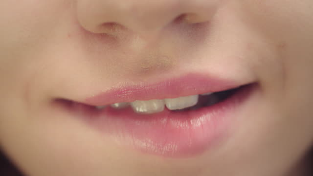 weibliches gesicht mit lächelndem mund beißt plumpe lippen. nahaufnahme frau beißt sexy lippen - lippen stock-videos und b-roll-filmmaterial