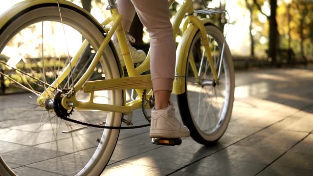 Female faceless legs walking by bicycle on paved road close up side view active lifestyle. Girl woman goes with vintage bike on street or green park. Healthy life summer outdoor activities