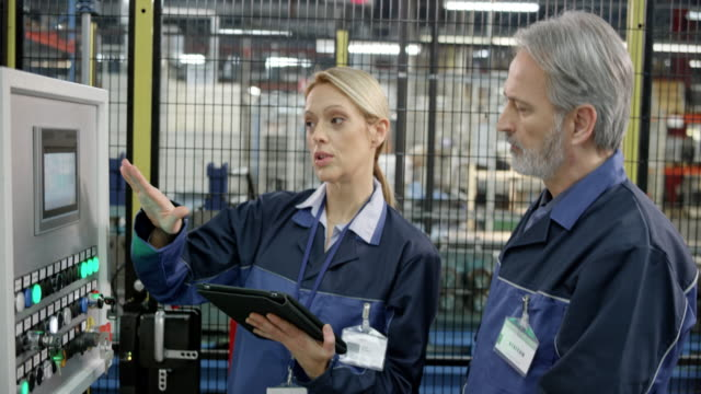 Video Female factory employee showing her male colleague the data entered into the touch screen on the machine's screen