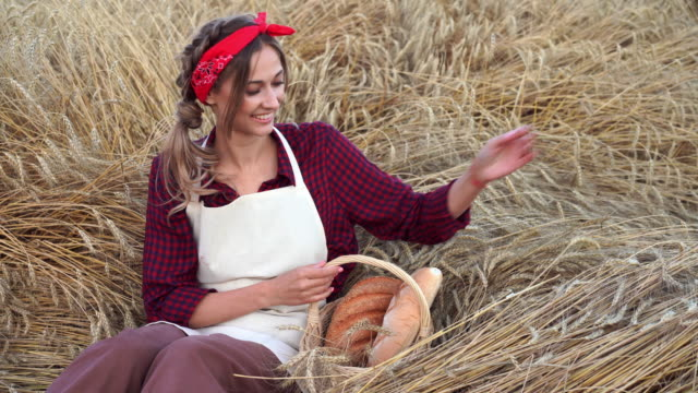 Female farmer sitting wheat agricultural field Woman baker holding wicker basket bread product