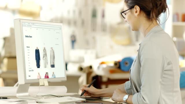 vidéos et rushes de styliste de vêtements féminins fonctionne avec tablette de dessin numérique sur son ordinateur personnel, elle conçoit le nouveau site web du magasin de détail en ligne. dans le studio ensoleillé de fond avec des tissus et des points de couture. - mode bureau