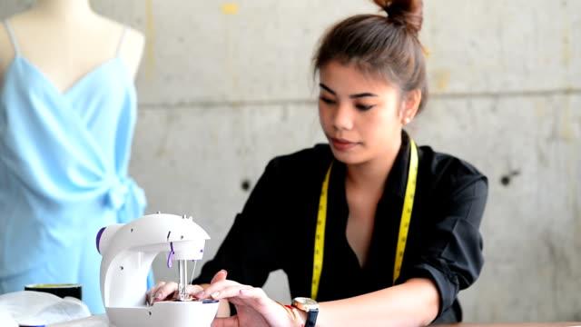 Femme styliste / couturière / couturière travaillant sur une Machine à coudre dans son atelier. - Vidéo