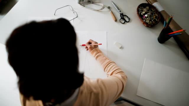 vídeos y material grabado en eventos de stock de diseñador de moda femenina dibujo en su estudio de sastre - bocetos de diseños de moda