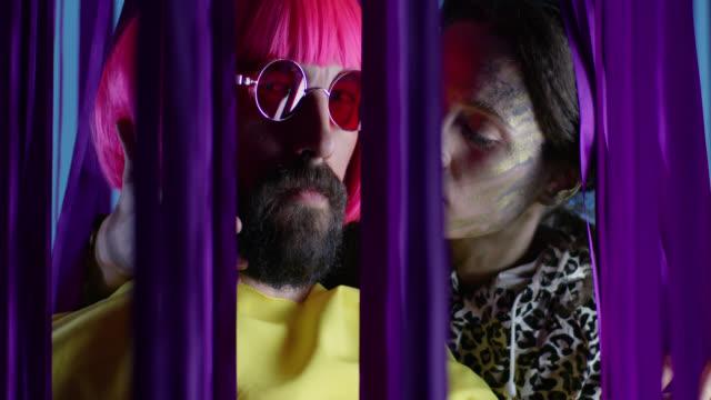 stockvideo's en b-roll-footage met vrouwelijke mannequin in fase make-up kussen mannelijke mannequin in roze pruik en zonnebril, het dragen van gele jas. video mode. - drag queen