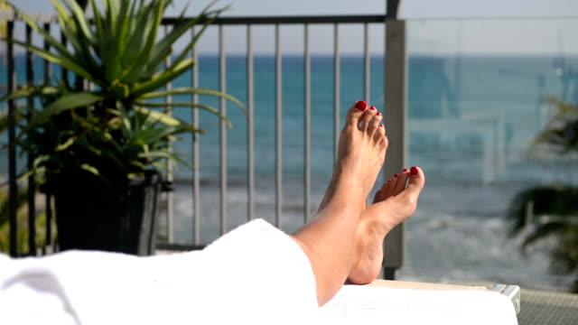 weibliche füße kreuzen auf dem balkon beim blick auf das meer - sauna und nassmassage stock-videos und b-roll-filmmaterial