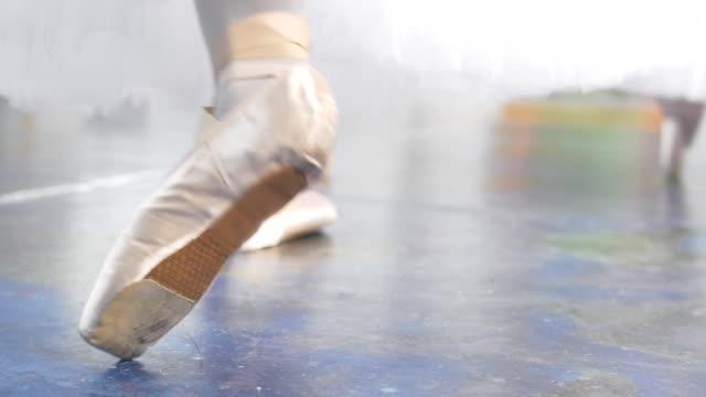 vídeos de stock e filmes b-roll de female feet dancing in pointe shoes in front of ballerinas performs a dance in a studio - tule têxtil