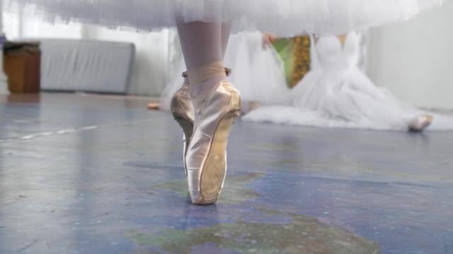 vídeos de stock e filmes b-roll de female feet in pointe shoes in front of ballerinas exercising in a studio - tule têxtil